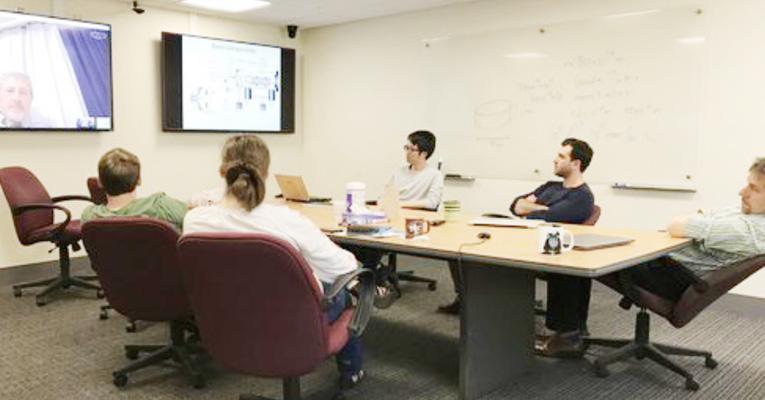 【写真】メリーランド大学で毎週行っているグループミーティングのようす。学生とスタッフが研究の話をする場だが、メンバーは世界各地に出張中であることが多いため、例えばこの写真の時は朝8時からSkypeで行っている。一枚のスライドで20分以上意見交換や質問をし合う、とても刺激的な時間(吉崎)。